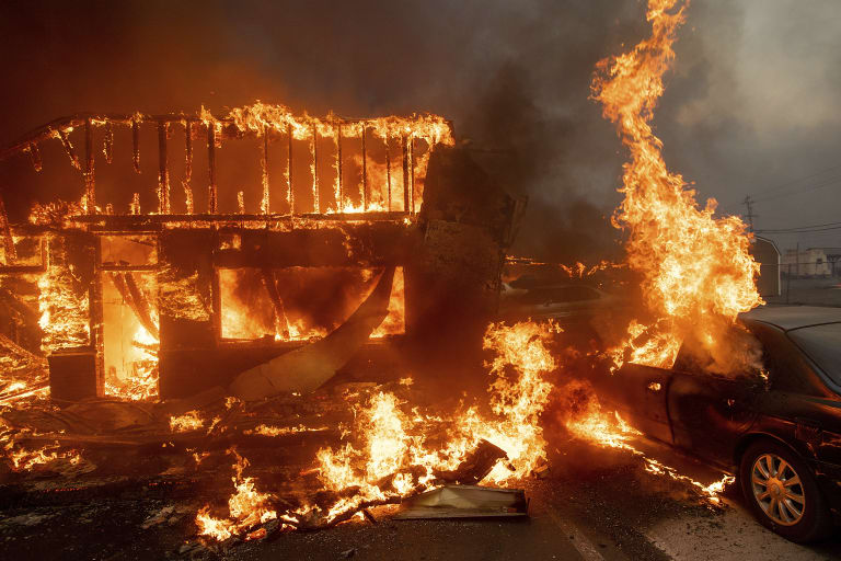Flames consume a car and building as the Camp Fire tears through Paradise.