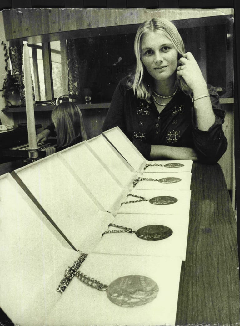 With her Olympic medals in 1975.