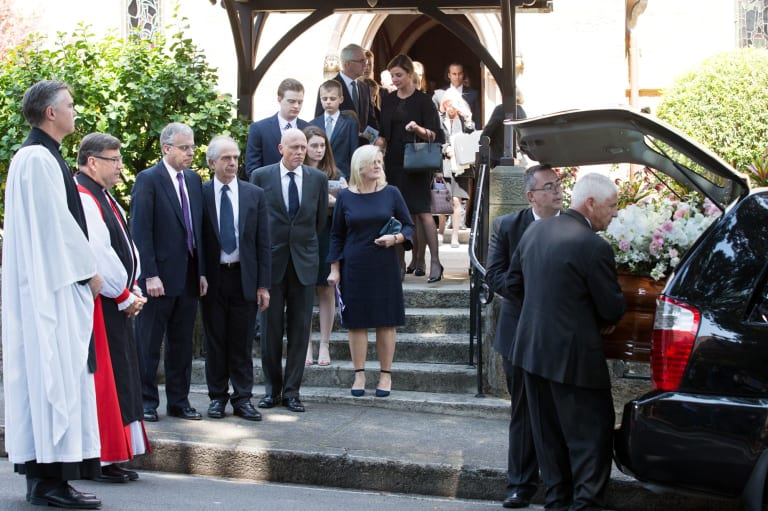 The sons of Lady Mary Fairfax, (L-R Warwick Fairfax, Garth Symonds, and Charles Fairfax) watch as her coffin is loaded into the hearse at her funeral in Darling Point, Sydney. 22nd September 2017.