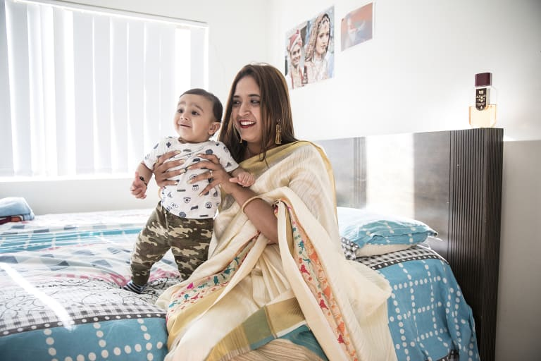 Himali sits on her bed with her 10-month-old nephew Prayaan.