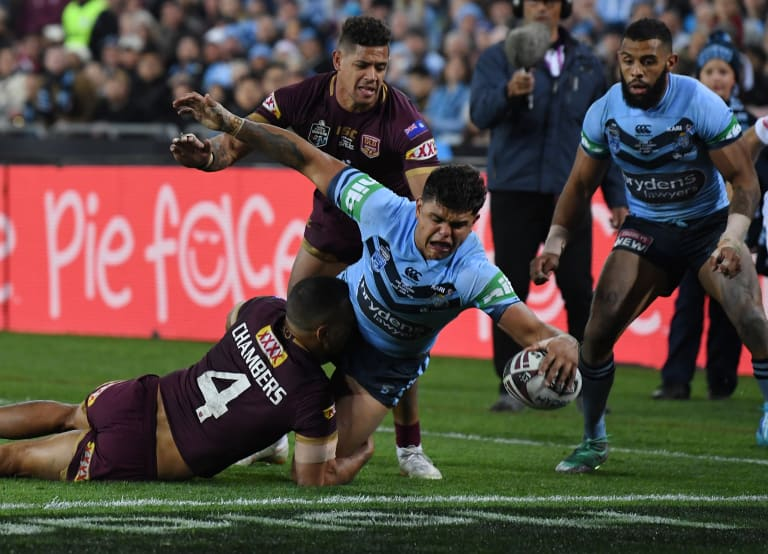 Big game player: Latrell Mitchell barges over for the Blues as Dane Gagai looks on.