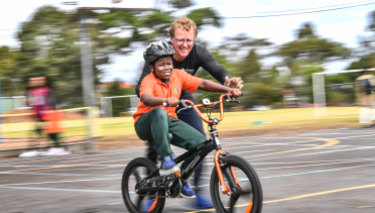 Smile says it all: Abdul Popoola masters a donated bike, his first, with help from Bart Sbeghen, co-founder of Dr Cranky's Bikes for Kids, at Clayton North Primary School.