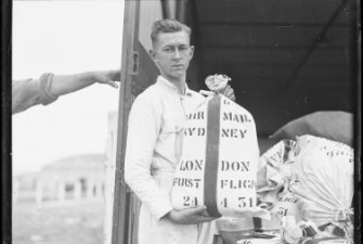 Young man loading the first air mail for England on to the Southern Sun, 24 April 1931