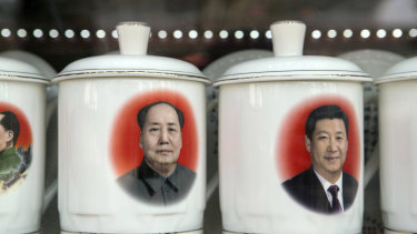 Porcelain cups featuring portraits of Chinese President Xi Jinping, right, and former Chinese leader Mao Zedong in a store window in Beijing,
