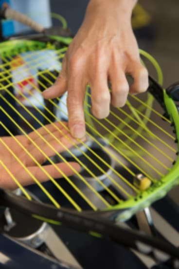 Every frame is different: Australian Open stringer Pin Lay hand-threads a polyester string into a racquet frame.