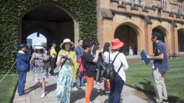 A tour guide takes a group of Chinese people for a tour of Sydney University in February.