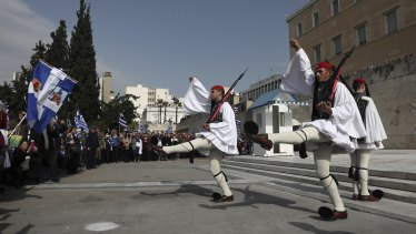 Protesters watch the changing of the Presidential Guard during the rally in Athens on Sunday.
