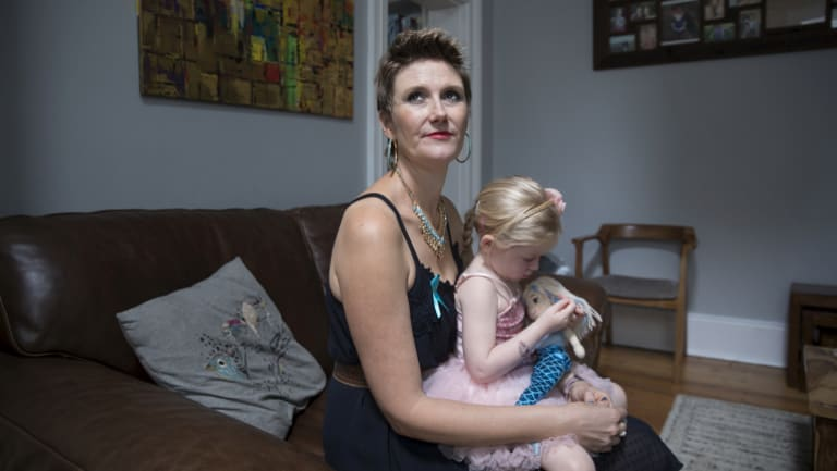 Caitlin Delany, who has stage four ovarian cancer, holding daughter Willow in their Sydney home.