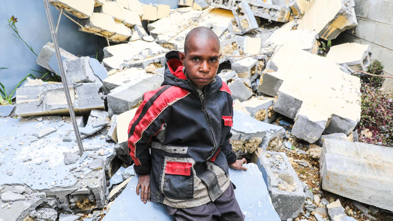 Abel Jeffery, 10, in front of the damaged Mendi School of Nursing, where 5 buildings were seriously damaged.