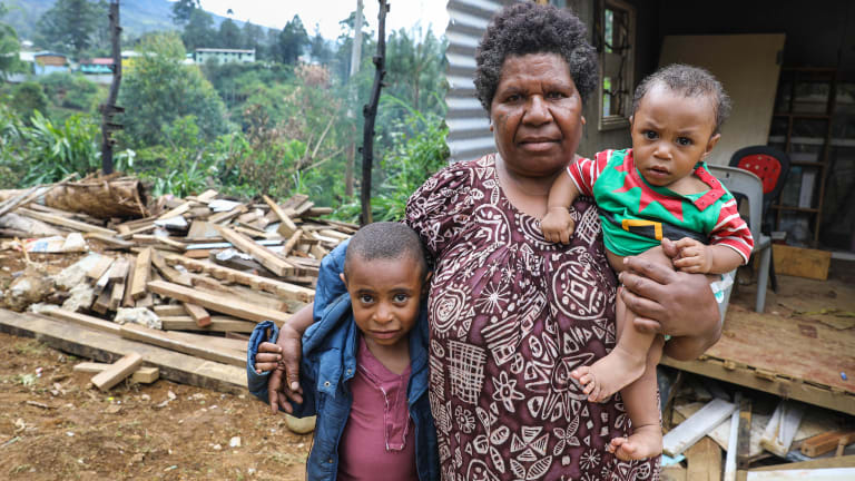 Pauline Johnson, 6, her mother Janette and brother Jford, 9 months, are living in temporary accommodation on the site where their two houses, home to four children and eight adults, were destroyed.