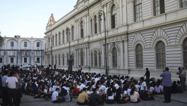 Students from a public school sit in an open area after being evacuated, in Veracruz, Mexico.