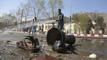 Afghan firefighters clean up the site of the deadly  bombing.