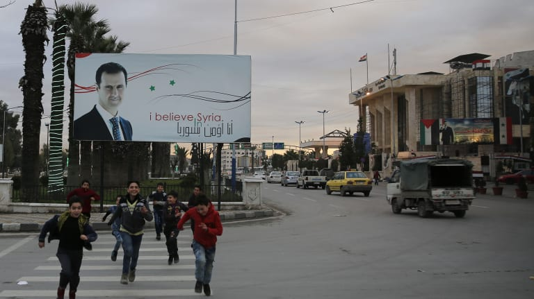 Syrian children cross an Aleppo street in front of a billboard of President Bashar al-Assad. A new report says Assad's chemical attacks on Syrians may have been enabled by North Korea.