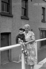 """""""MARGARET THOMPSON shows her two-year-old grandson PAUL the cottage in Susannah Place — dated 1844 — where his father was born. Mrs Thompson has lived around The Rocks all her life, and was baptised and married at St. Patrick's, Church Hill."""""""