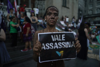 "An activists covered in mud poses with a sign that reads ""Vale assassin"" during a demonstration on the front steps of Sao Paulo's Cathedral in Brazil last week."