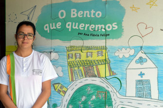 "Eliene Geralda dos Santos, Bento Rodrigues' school principal, at the school's temporary premises in Mariana, in Brazil's Minas Gerais state in November.  In the background a student's drawing depicts ""The Bento we wish for""."