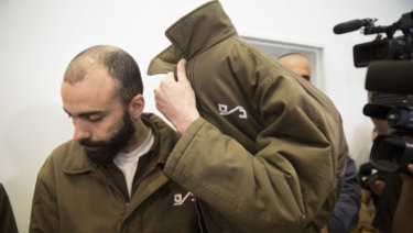 French consulate worker Romain Franck, a French employee of France's Consulate in Jerusalem, covers his face during a hearing at the district court in in the southern Israeli city of Beersheba, on Monday.
