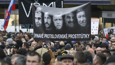 Demonstrators hold a poster reading 'Dirty anti-Slovak prostitutes' with Prime Minister Robert Fico in the middle, his Interior Minister Robert Kalinak (to Fico's right), and national police chief Tibor Gaspar, right, during an anti-government rally in Bratislava, Slovakia, on  March 9.