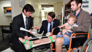 Surgeon Dr Michael Wagels and Queensland Health Minister Cameron Dick discuss the operation with Reuben Lichter and his son, William.