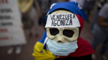 A woman with a message on her forehead that reads  'Venezuela agonises' during a protest demanding the government attend to the country's health crisis.