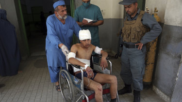 An injured man is moved by wheelchair at a hospital following the suicide attack in front of Kabul University.