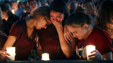 Students weep during a candlelight vigil for the victims at Marjory Stoneman Douglas High School.
