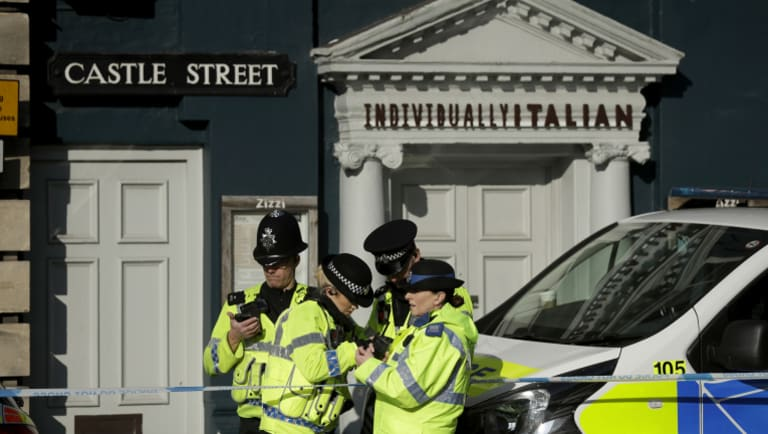 Police officers stand outside a Zizzi restaurant. Investigators are trying to determine how Skripal was poisoned.
