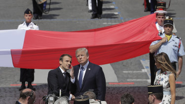 French President Emmanuel Macron talks with U.S President Donald Trump next to a huge French flag after the Bastille Day parade in Paris in  July.