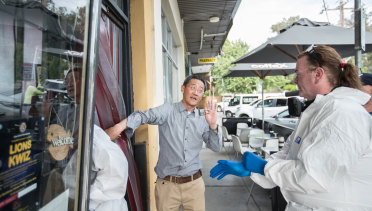 Owner Sean Wang letting in the forensic cleaners to the shop.