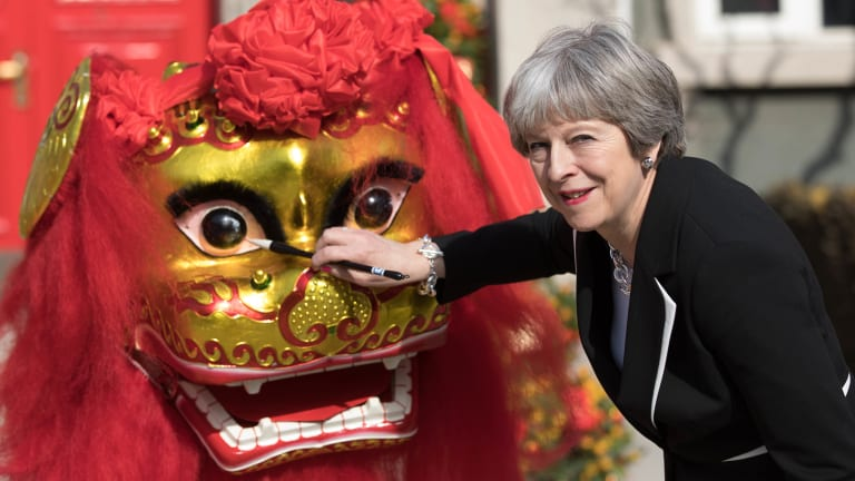 Theresa May dots the lion's eyes during a traditional lion dance ceremony outside the British embassy in Beijing.