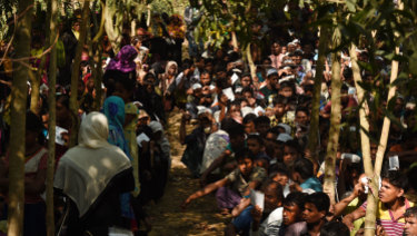 Rohingya refugees sit in a queue at a Red Cross distribution point in Burma Para refugee camp.  Cox's Bazar, last November.