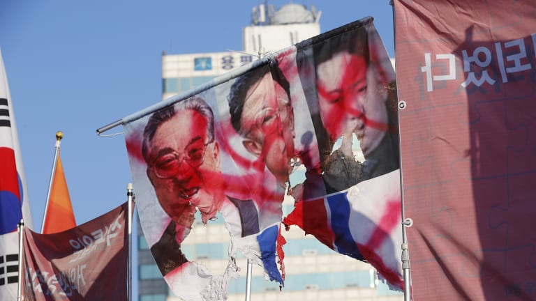 A ripped flag with the portraits of late North Korean leaders, from left, Kim Il-sung, Kim Jong-il and current leader Kim Jong-un during a pro-US, anti-North Korea rally near the Pyeongchang Olympic Stadium.