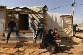 A woman sits with her grandson and other children in front of the temporary shelters in Saideh camp in the Bekaa Valley in Lebanon.