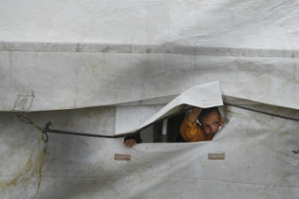 On the outside looking in: a child peeks through the flap of a tent in the foreign section of al-Hawl camp in Syria.