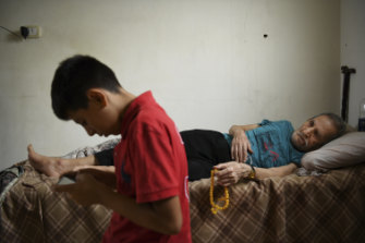 Syrian refugees Mohammad al-Deraai, 13, watched by his ill uncle Sobhi al-Deraai in the family apartment in Ain al-Hilweh.