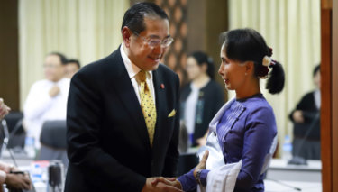 Myanmar's Foreign Minster and de facto leader Aung San Suu Kyi, right, shakes hands with Surakiart Sathirathai, left, a member of the Advisory Commission on Rakhine State on Monday.