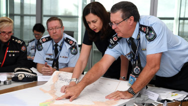 Queensland Premier Annastacia Palaszczuk (centre) is briefed by Police Commissioner Ian Stewart (right) on the floods in the state's north at the State Emergency Complex in Brisbane.