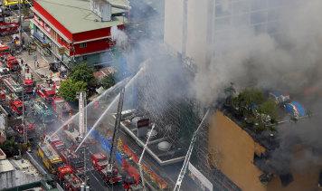 Fire crews battle a fire at the  Manila Pavillion Hotel on Sunday.
