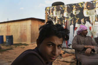 Mohammad, 14, sits with his father Abdelmeneim Moustafa, 54, in Saideh camp after a day shift at a construction site.