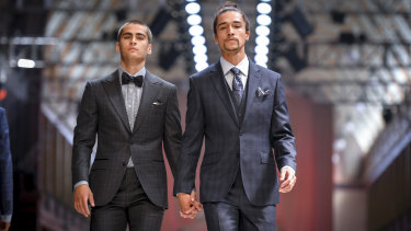 Two male models dressed as grooms hold hands at rehearsals for the bridal runway at Melbourne Fashion Festival.
