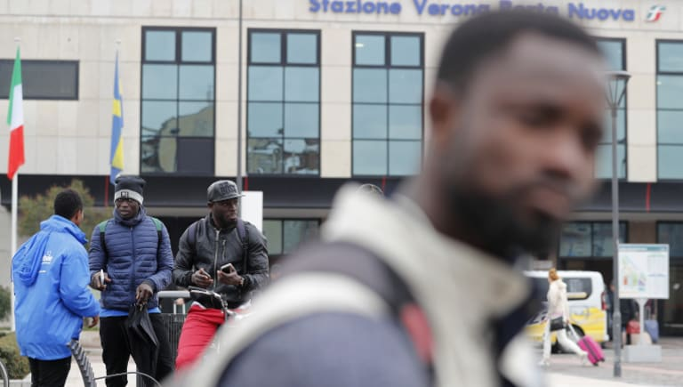 Migrants stand in front of Verona's railway station. Racist and anti-Semitic expressions have been growing more bold, widespread and violent in Italy.