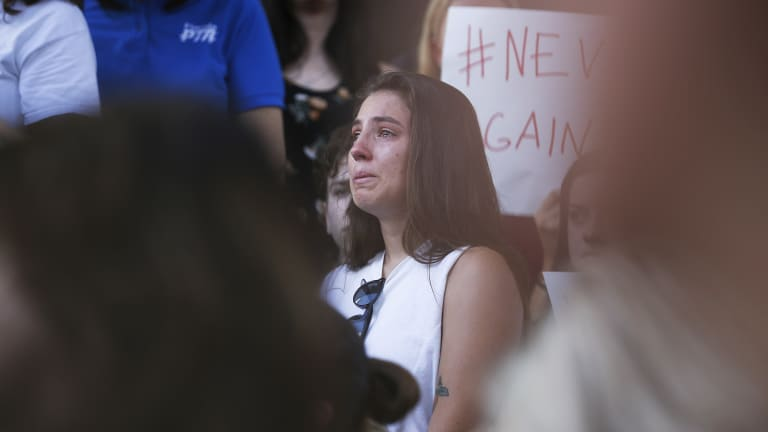 A young woman cries during a protest against guns on the steps of the Broward County Federal courthouse in Fort Lauderdale.