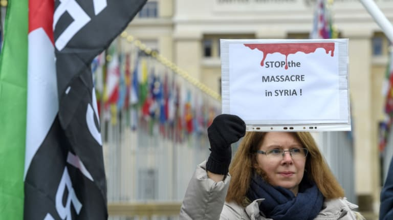 Demonstrators hold banners in solidarity with the Syrian people during a rally against the bombing of Syria on the Place des Nations, in front of the European headquarters of the United Nations in Geneva.
