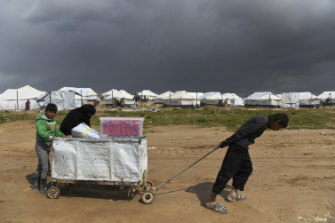 A woman and two boys push a cart near the fence line of the foreign section of al-Hawl camp.