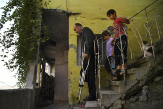 Wafa Gourani, 47, a dessert chef from Aleppo and now an amputee living in Istanbul, negotiates the steps from his apartment followed by his two youngest sons Hamza, 6, and Abdullah, 8.