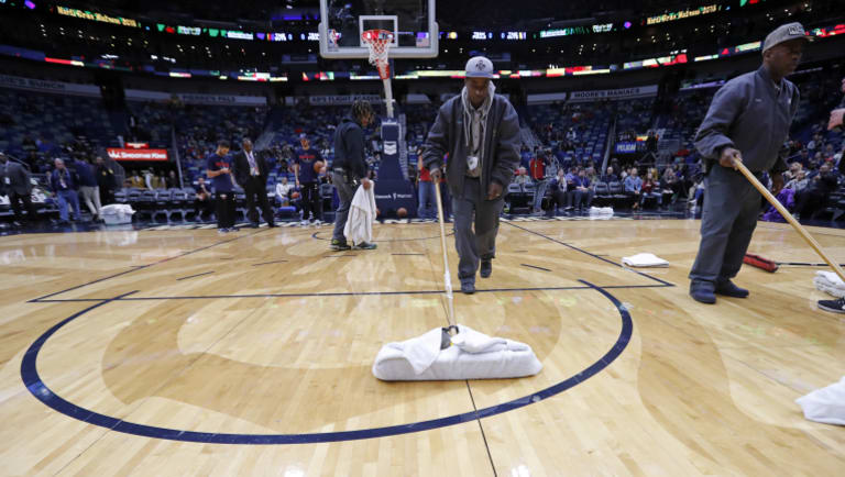 Workers mop the court.
