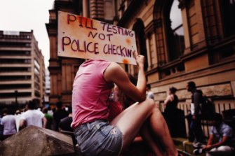 An attendee holds up a sign at a pill testing rally held at Sydney's Town Hall on Saturday.