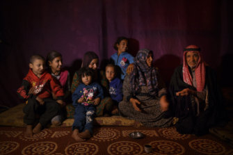 Abir (second from right) talks to her husband Mahmoud, 70, inside their temporary shelter in the Bekaa Valley.