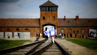 Young visitors with Israeli flags walk on railway tracks on the grounds of the former German Nazi death camp Auschwitz-Birkenau near Oswieciem, Poland, in 2015.
