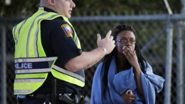 An employee wrapped in a blanket talks to a police officer after she was evacuated at a FedEx distribution center where a package exploded.